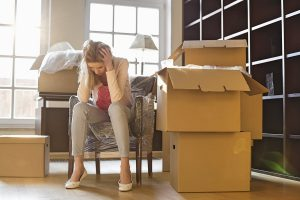 A woman sits in a chair with her head in her hands. There are boxes all around her. She is exhausted and frustrated iwth moving.