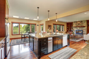 Photo of kitchen with large center island overloooking dining area and family room with stone fireplace